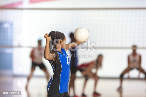 A teenaged girl in a blue jersey is playing in a volleyball match. She is about the serve the ball. They are playing in a school gym.