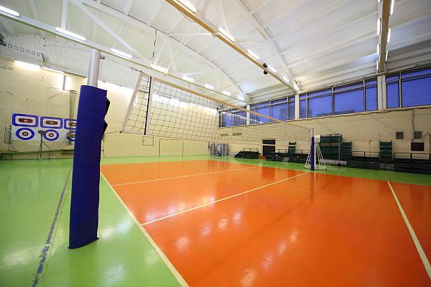 Volleyball net inside lighted school gym hall stock photo