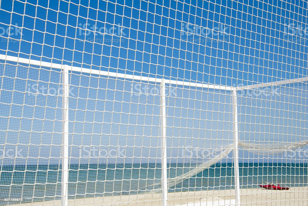 Volleyball net with red boat on the beach. Lizenzfreies stock-foto