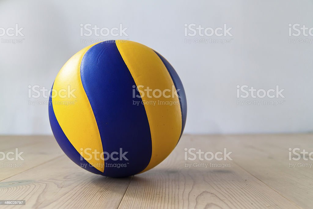 Blue and yellow volleyball on wooden floor