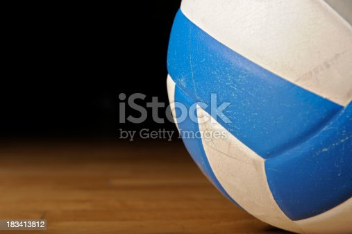 A used leather volleyball resting on a wood gym floor. Area available on left side for text.