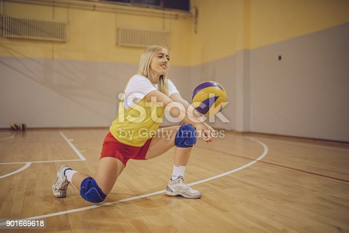 Female high school volleyball player standing with a ball
