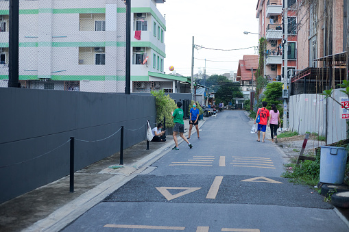 Volleyball playing thai students in residential area at afternoon near university CRU. Students are playing in street with volleyball between condominiums. At right side  women are walking. One woman is sitting on street