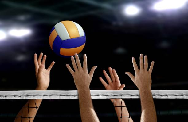 volleyball spike hand block over the net - volleyball sport stock photos and pictures