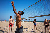 Young people playing volleyball at the beach
