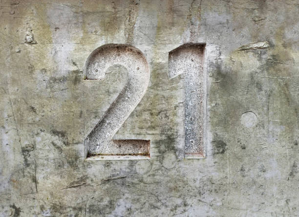 Volume Number 21 on a dirty, concrete wall stock photo