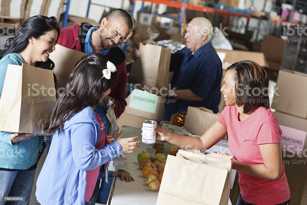 Volunteer accepting donations from family at food bank stock photo