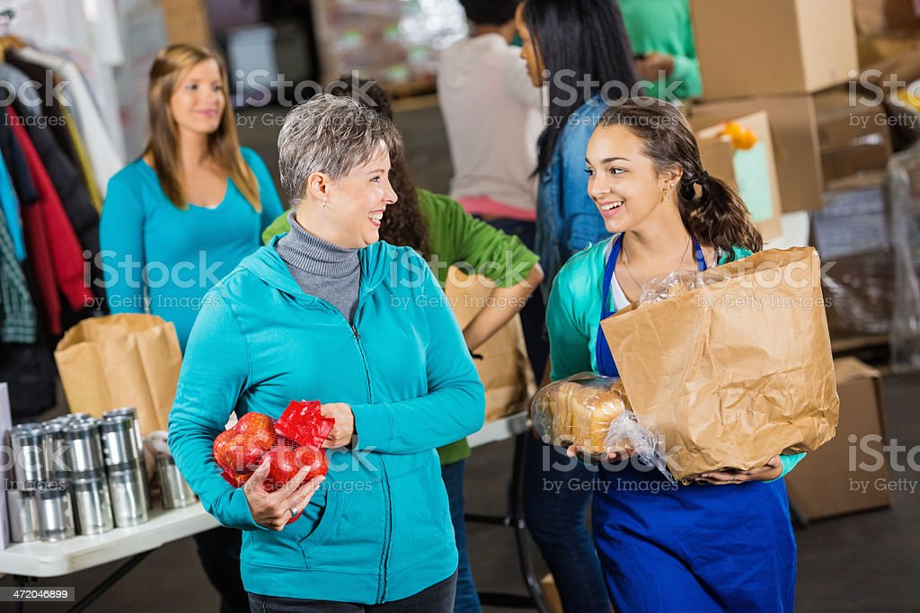 Volunteer assisting senior woman with grocery donations at food bank stock photo