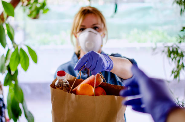 Volunteer Bringing food to old and disability people in quarantine Woman delivering food in paper bag during Corona outbreak.Female volunteer holding groceries in the house porch in COVID-19 outbreak charitable donation stock pictures, royalty-free photos & images
