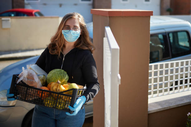 Volunteer bringing groceries at house during the pandemic stock photo