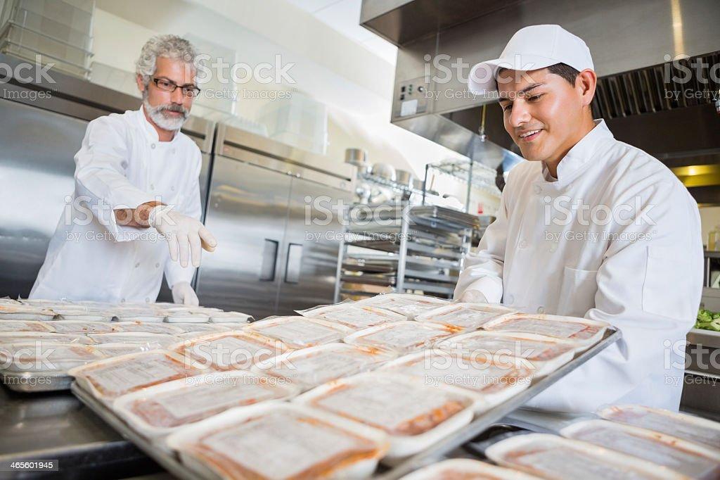 Volunteer chefs preparing frozen meals for food bank stock photo