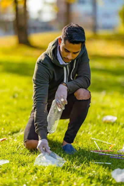Freiwillige reinigen Müll auf Gras am Park – Foto