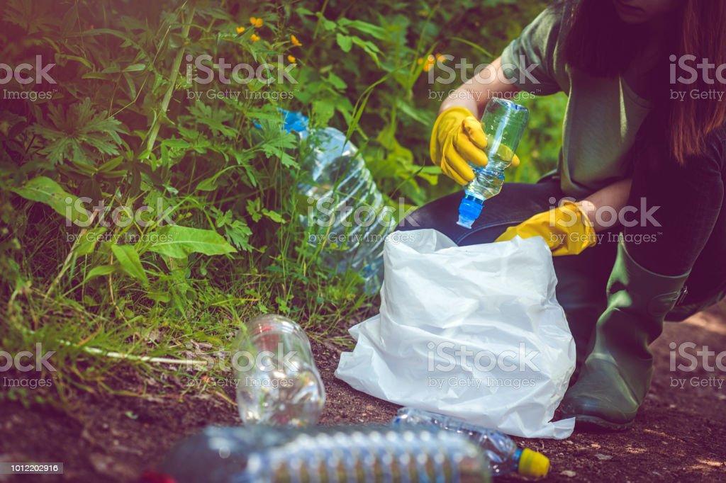 Freiwilliger sammelt Plastikflaschen im freien – Foto