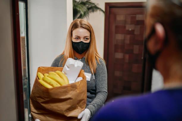 Volunteer Delivering Food To Elderly People During Lockdown stock photo