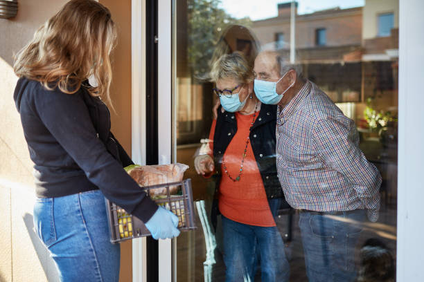 Volunteer delivers groceries to senior couple during pandemic stock photo