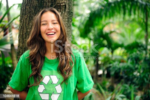 young volunteer: environmentalist  in the forest wearing a green recycling t-shirt