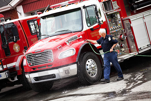 Volunteer Firefighter washing fire truck stock photo