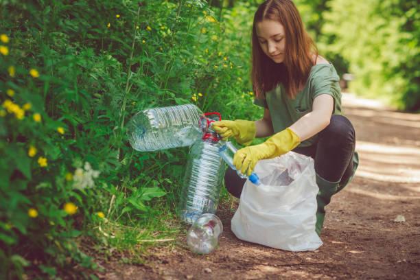 ragazza volontaria raccoglie spazzatura - bottiglie di plastica in primavera o in estate all'aperto - ambientalista foto e immagini stock