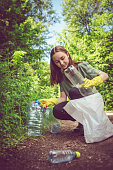 Volunteer girl in yellow gloves collects plastic garbage