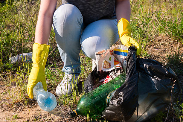 Volunteer girl in yellow gloves collects garbage selective focus Volunteer girl in yellow gloves collects garbage selective focus environmental cleanup stock pictures, royalty-free photos & images