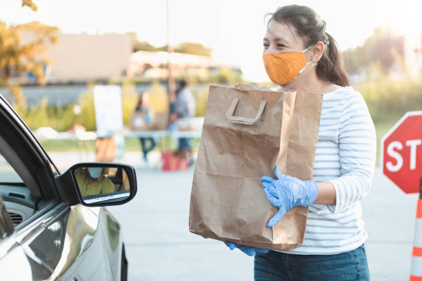 Volunteer gives out food during food drive stock photo
