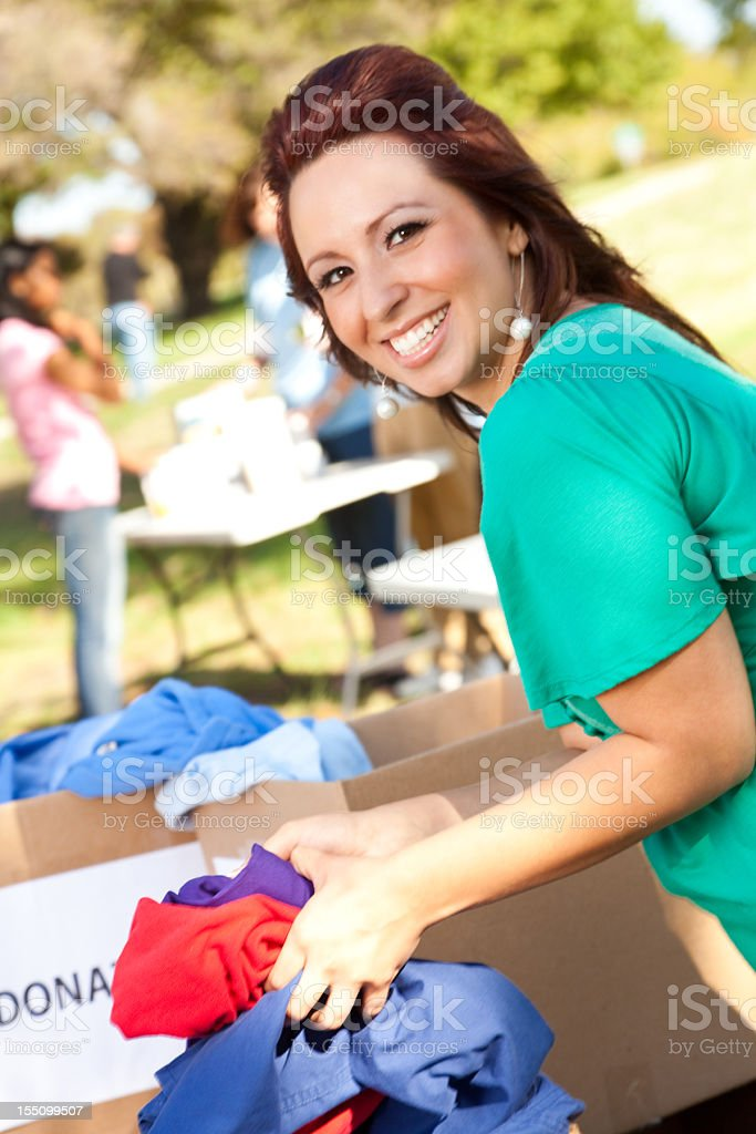 Volunteer going through donations boxes at a donation center royalty-free stock photo