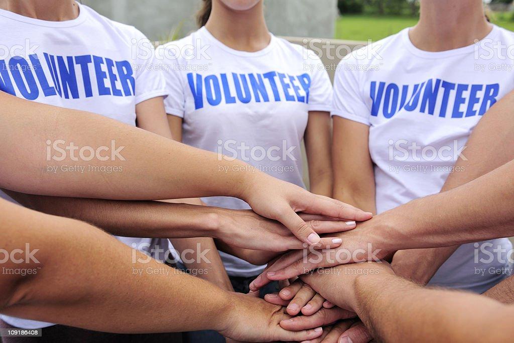 Voluntarios grupo de las manos juntas - foto de stock