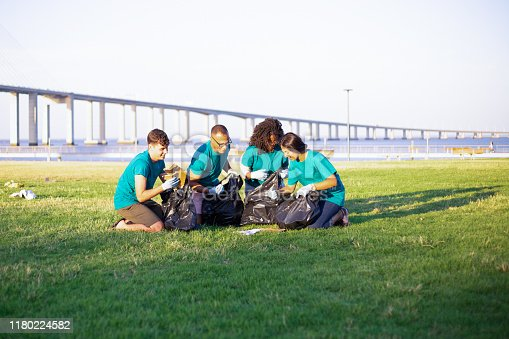 Volunteer group sorting waste and cleaning city lawn. Men and women sitting on grass, picking up litter into plastic bags. Garbage collection concept