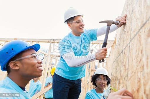 Mid adult Hispanic male volunteer is standing on a ladder and hammering a nail into wall. He is helping build home for charity. He smiles confidently as team of volulnteers observe him. They are wearing hard hats, safety glasses and light blue volunteer t-shirts.
