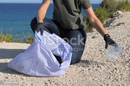 962184460 istock photo Volunteer hand with protective glove cleaning beach from plastic. Woman picking up plastic bottle trash and putting into plastic bag for recycle 1250537944