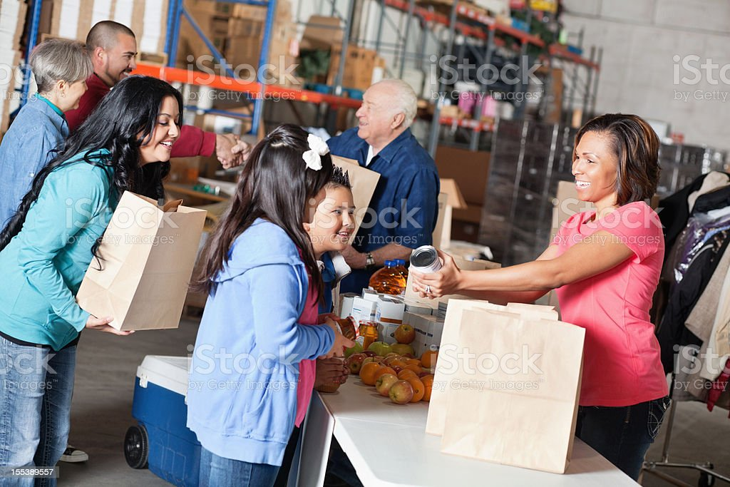 Volunteer handing out food donations to family royalty-free stock photo