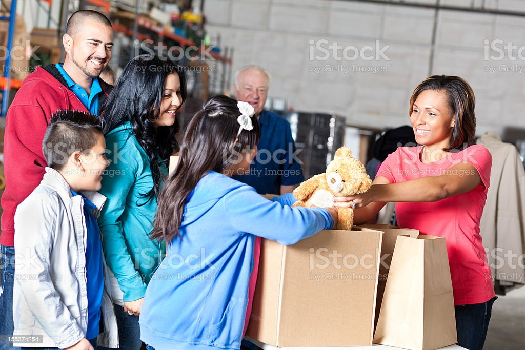 Volunteer handing out toy donations to family royalty-free stock photo