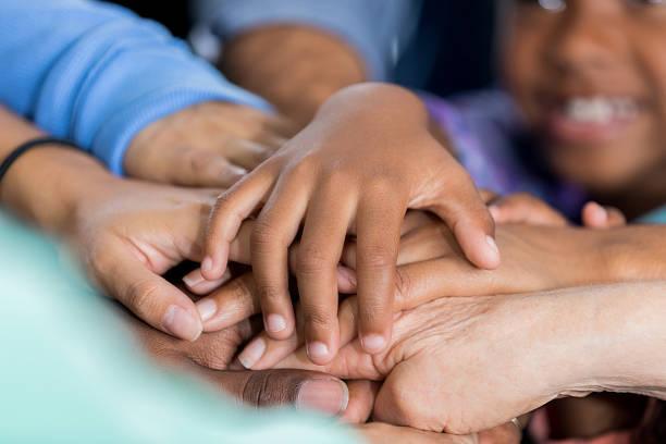 volunteer hands together in unity - ayuda humanitaria fotografías e imágenes de stock