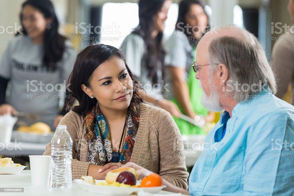 Volunteer avoir repas avec homme senior à Soupe populaire - Photo