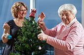 istock Volunteer helping senior decorate her Christmas Tree 123466783