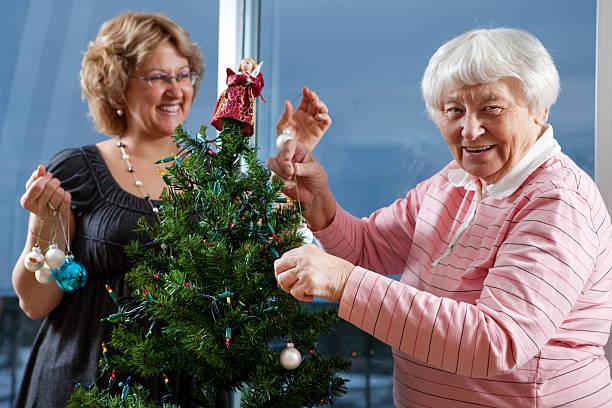 Volunteer helping senior decorate her Christmas Tree stock photo