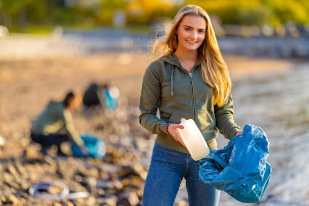 Volunteer holding bottle and garbage bag at beach Portrait of confident young woman holding bottle and garbage bag. Smiling volunteer is cleaning beach on sunny day. She is wearing casuals. social responsibility stock pictures, royalty-free photos & images