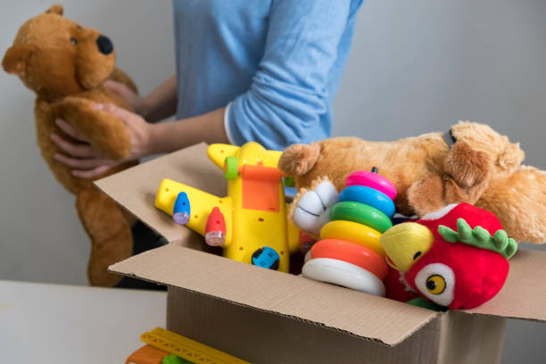 volunteer holding donation box with old toys stock photo