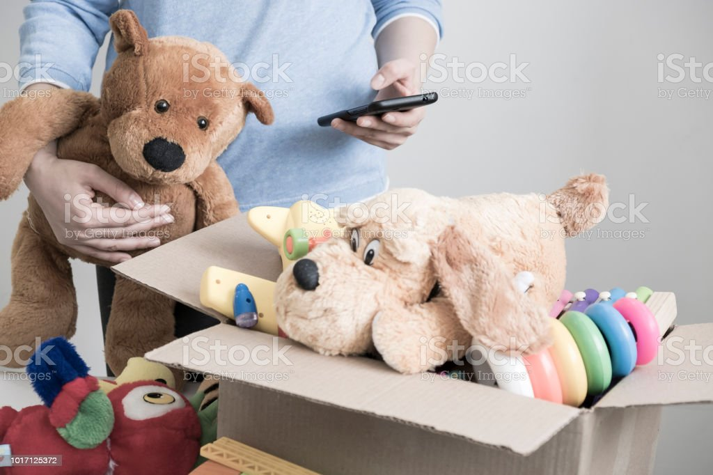 Male volunteer holding donation box with old toys