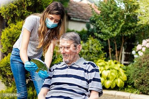 Beautiful young adult woman is shaving her grandfather's beard at front yard of his house during the quarantine period of coronavirus