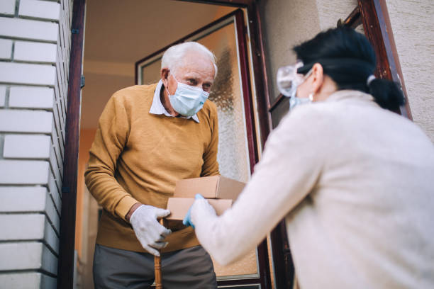 Volunteer in mask gives an elderly man boxes with food stock photo