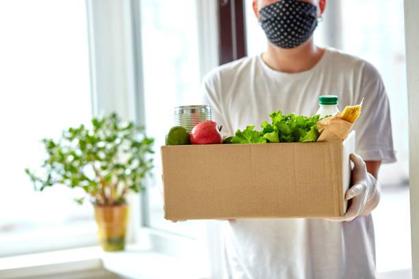 Freiwillig in weißer Schutzmaske und Handschuhen Lieferung Spendenbox zu Hause. Kurier Mann mit Packbox mit Lebensmitteln, kontaktlose Lieferung. Service Quarantäne Pandemie Coronavirus. – Foto