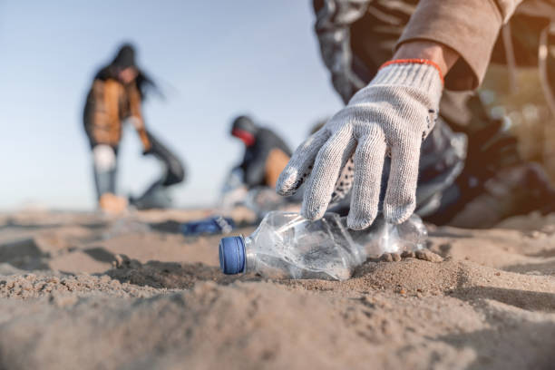 volunteer man collecting trash on the beach. ecology concept - plastica foto e immagini stock