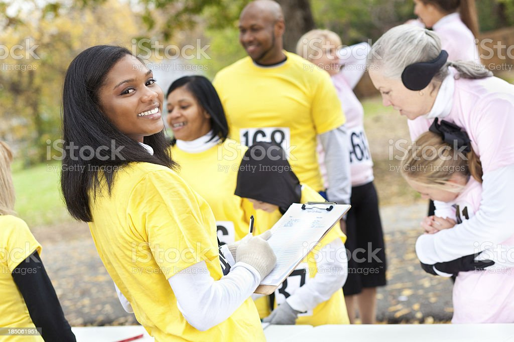 Volunteer signing up charity race runners royalty-free stock photo