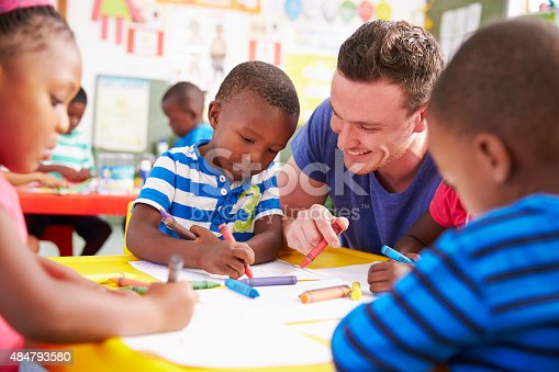 istock Volunteer teacher helping a class of preschool kids drawing 484793580