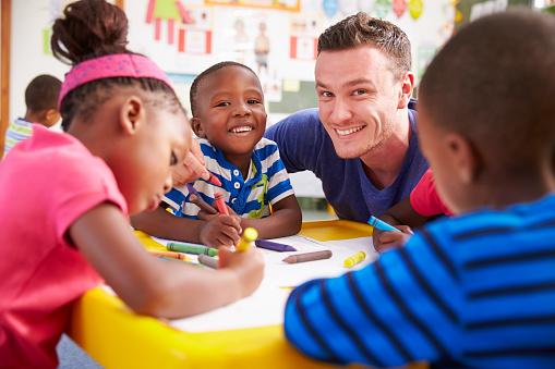 Volunteer Teacher Helping A Class Of Preschool Kids Drawing Stock Photo - Download Image Now
