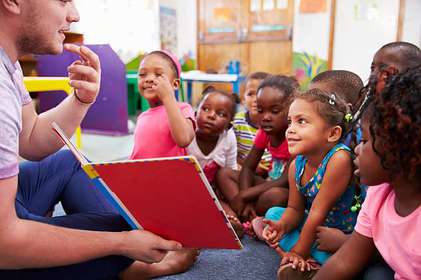 volunteer teacher reading to a class of preschool kids - community project stock photos and pictures