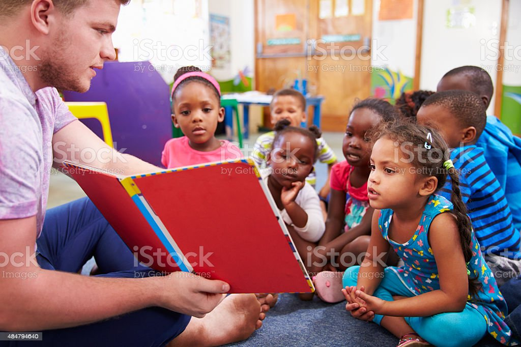 Volunteer teacher reading to a class of preschool kids stock photo