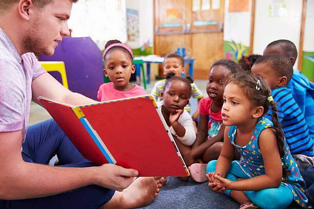 volunteer teacher reading to a class of preschool kids - elementary age stock photos and pictures