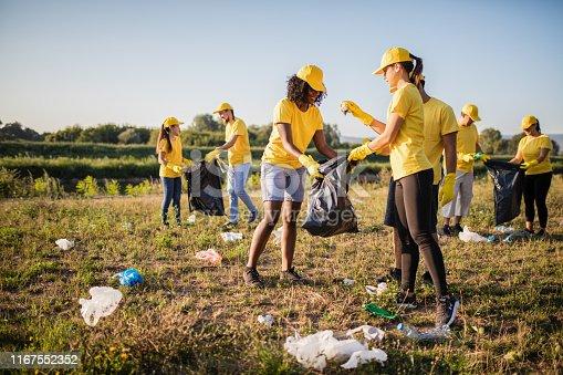 Volunteer together pick up trash in the park